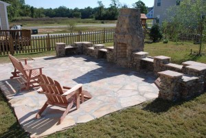 landscaped patio and rock walls with outdoor stone fireplace at charlies antiques in williamsburg va